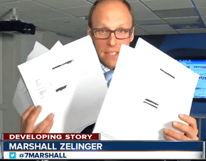 KMGH Denver reporter Marshall Zelweger holds up some of the emails received in the newsroom from victims that had new iPhone 6 smartphones billed to their account. (Image: KMGH-TV/Denver)